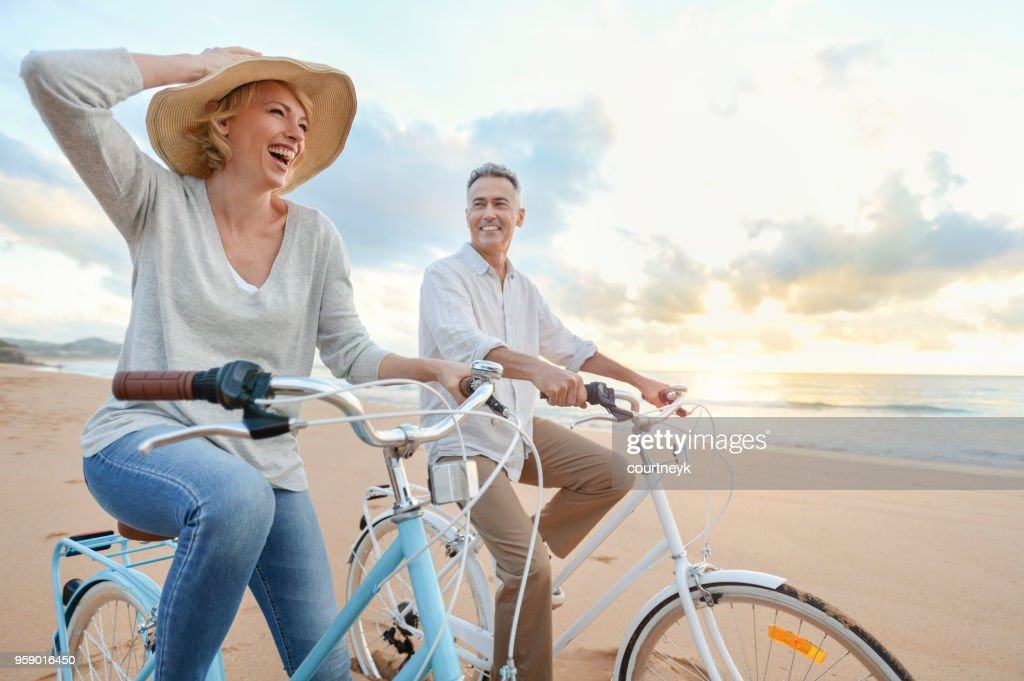 Mature couple cycling on the beach at sunset or sunrise. : Stock Photo