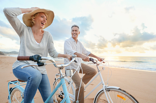 Mature couple cycling on the beach at sunset or sunrise. 959016450