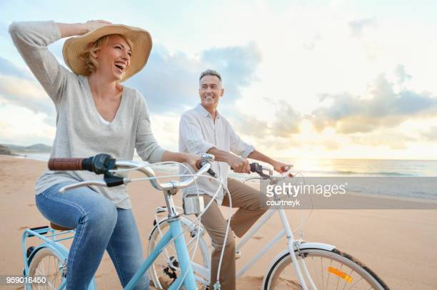 mature couple cycling on the beach at sunset or sunrise. - esposa imagens e fotografias de stock
