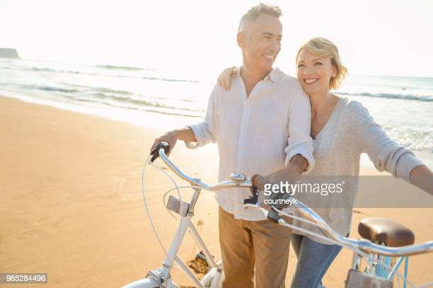 mature couple cycling on the beach at sunset or sunrise - baby boomer stock pictures, royalty-free photos & images