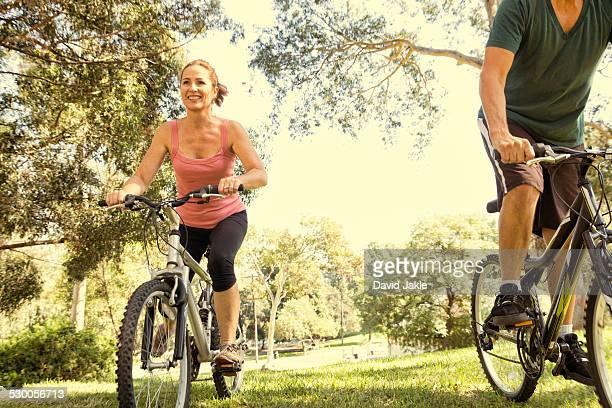 Mature couple cycling through park