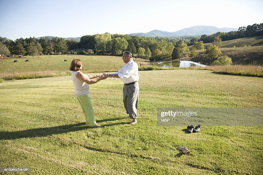 Mature couple dancing in field : Foto stock