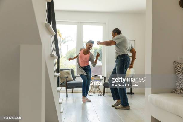 mature couple dancing in living room - disruptaging stock pictures, royalty-free photos & images