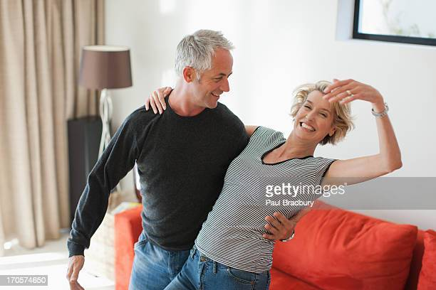 mature couple dancing in living room - 45 49 years stock pictures, royalty-free photos & images