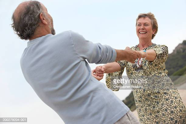 Mature couple dancing on beach, smiling, low angle view