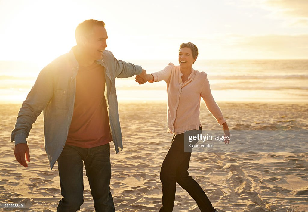 Mature couple dancing on the beach at sunset : Stock Photo
