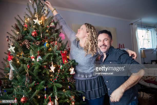 Älteres paar dekorieren Weihnachtsbaum zu Hause.
