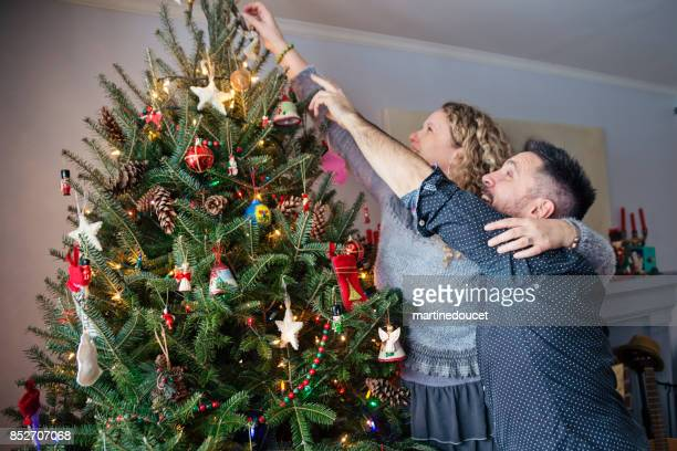 """mature couple decorating christmas tree at home. - """"martine doucet"""" or martinedoucet stock pictures, royalty-free photos & images"""