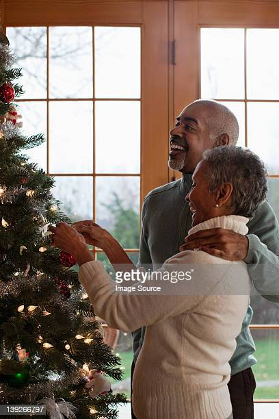 Mature couple decorating Christmas tree