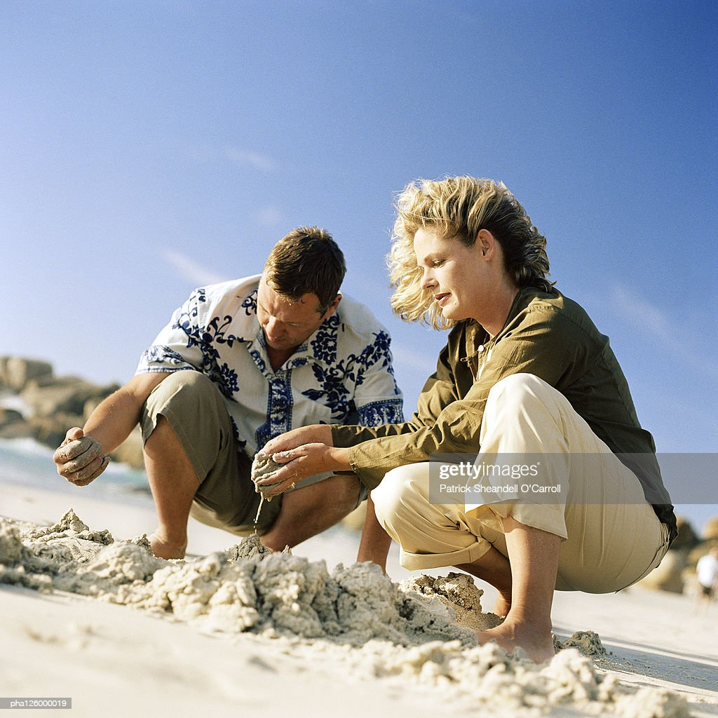 Mature couple digging in sand : Stockfoto