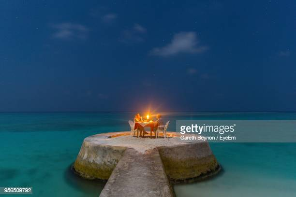 mature couple doing candlelight dinner on pier in sea - idyllic stock pictures, royalty-free photos & images