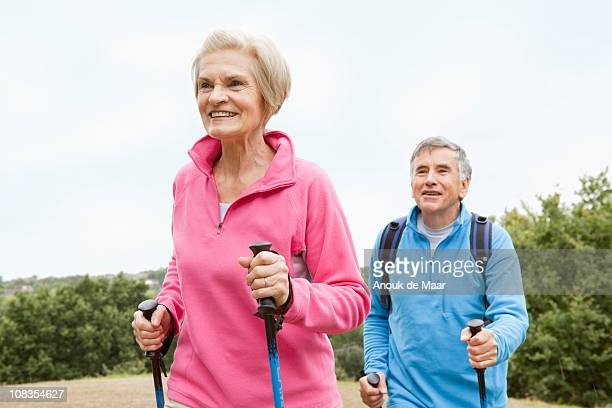 mature couple doing nordic walking - 65 69 jahre stock-fotos und bilder