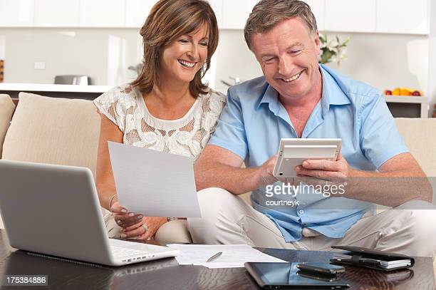 Mature couple doing paperwork with a calculator