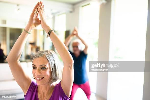 pareja madura haciendo pilates y yoga en su hogar - último cuarto deportes fotografías e imágenes de stock