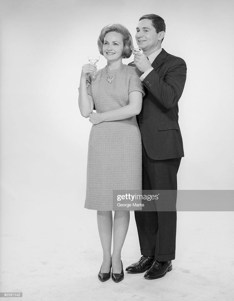 Mature couple drinking cocktails, studio shot : Stock Photo