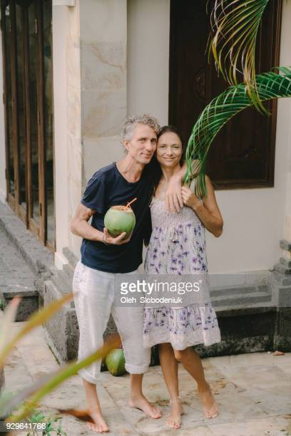 mature couple drinking  coconut on villa - expatriate stock pictures, royalty-free photos & images