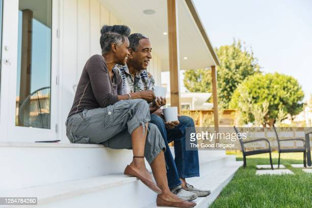 mature couple drinking coffee on porch - mature couple stock pictures, royalty-free photos & images