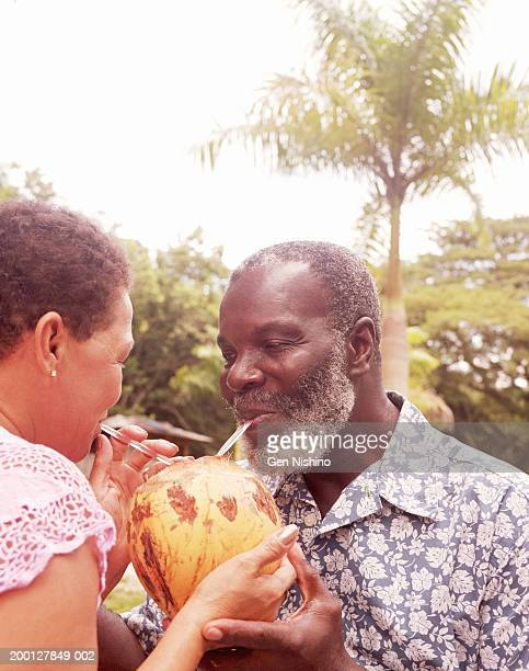 Mature couple drinking from one coconut, close up