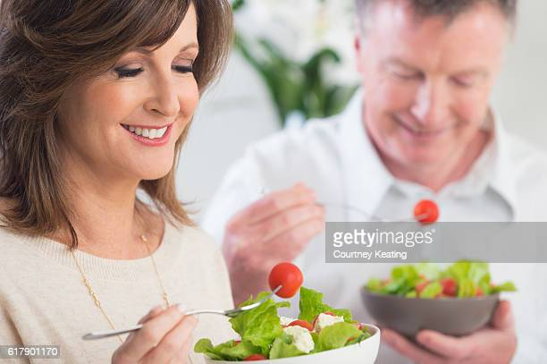 Mature couple eating a healthy salad.