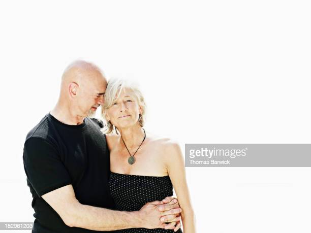 Mature couple embracing against white background