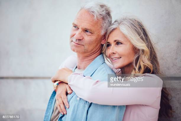 Mature couple embracing and relaxing against cement wall outdoors