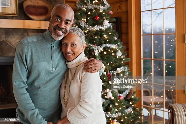 Mature couple embracing by Christmas tree, portrait
