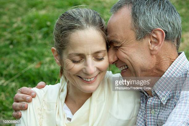 Mature couple embracing, eyes closed