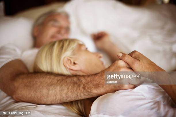 mature couple embracing in bed - love stock pictures, royalty-free photos & images