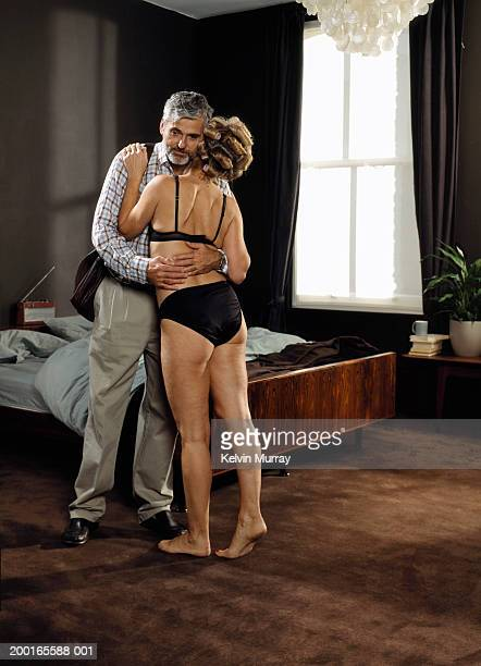Mature couple embracing in bedroom, woman wearing underwear