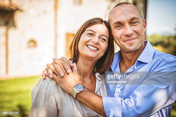 mature couple embracing in front of their house