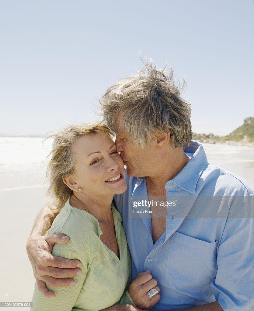 mature couple embracing on beach man kissing woman stock photo