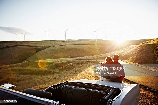 Mature couple embracing on car watching sunset