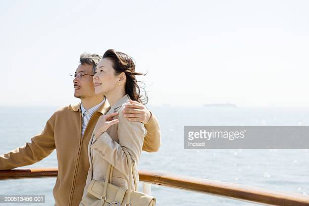 Mature couple embracing on deck of cruise ship, smiling, side view