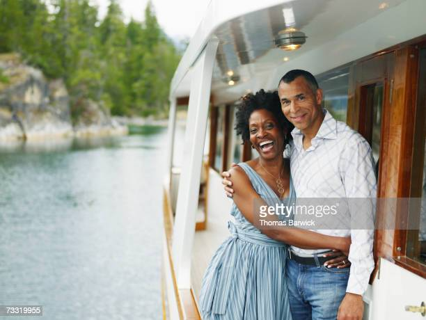mature couple embracing on yacht, portrait - ricchezza foto e immagini stock
