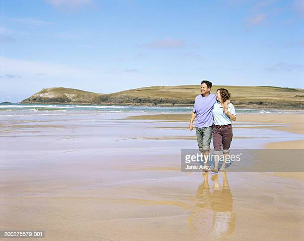 Mature couple embracing, walking on beach