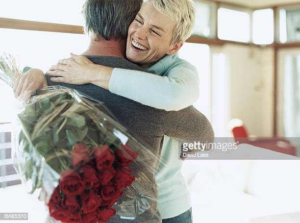 Mature couple embracing, woman holding bunch of red roses