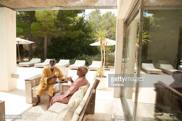 mature couple enjoy a poolside drink - villa stock pictures, royalty-free photos & images