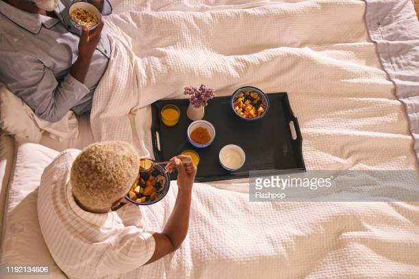 mature couple enjoy breakfast in bed - anniversary stock pictures, royalty-free photos & images