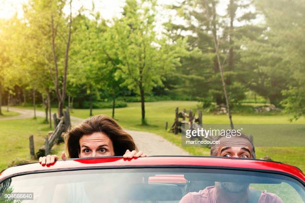 Mature couple enjoying a ride in red convertible car.
