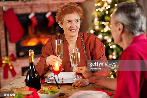 Mature couple enjoying in Christmas dinner.