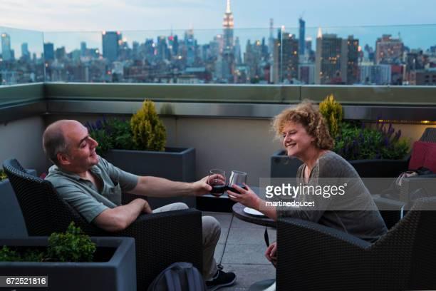 Mature couple enjoying New-York skyline at happy hour.