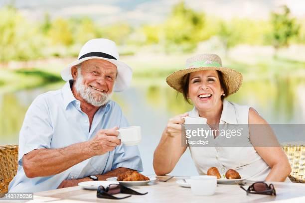 Pareja madura disfrutando de té en la terraza junto al lago