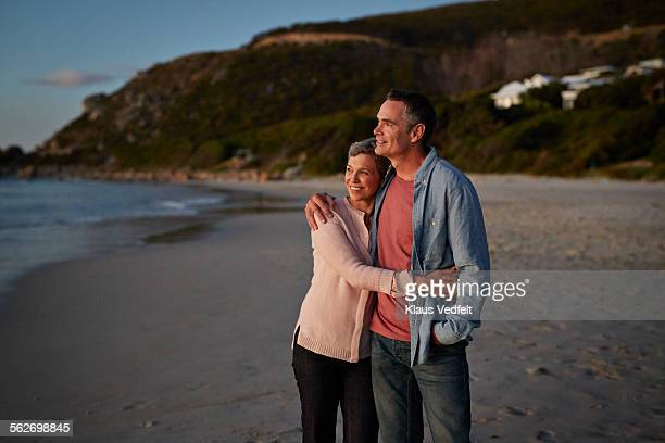 Mature couple enjoying the view on beach at dusk