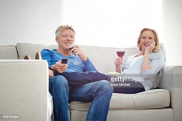 Mature couple enjoying watching movie at home