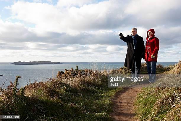 Mature couple enjoying winter walk on coastal path
