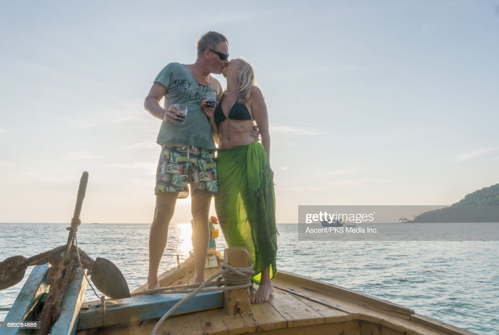 Mature couple enjoys wine on wooden deck at sunset : Stock Photo