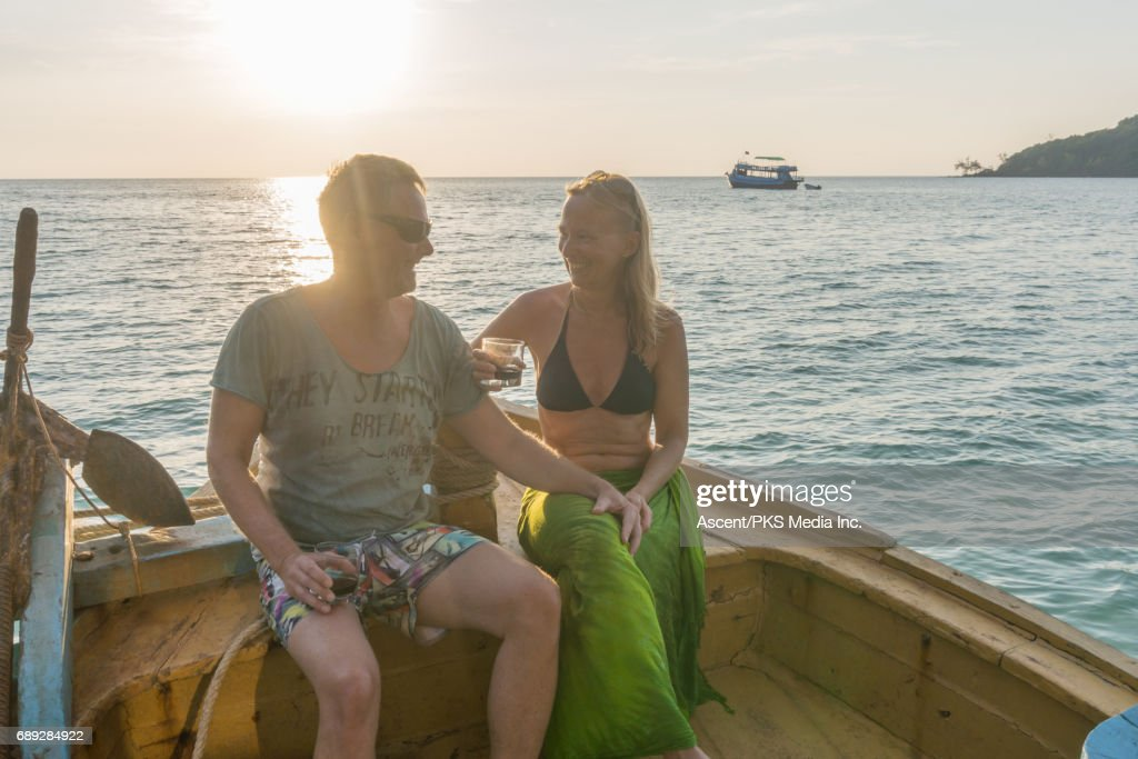 Mature couple enjoys wine on wooden deck at sunset : Stockfoto