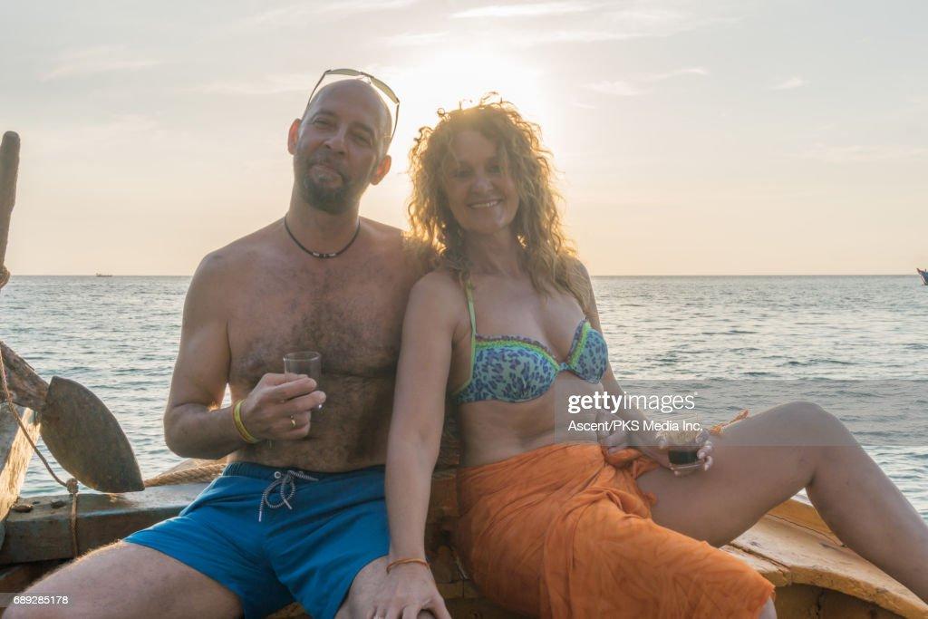 Mature couple enjoys wine on wooden deck at sunset : Stock Photo