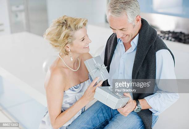 Mature couple exchanging anniversary gifts