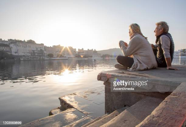 mature couple explores a ghat at sunrise, looks out across lake while sipping hot beverage - early retirement stock pictures, royalty-free photos & images